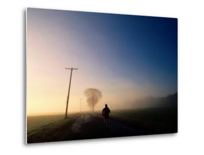 A Lone Jogger Runs Down a Rural Road in Early Morning Fog-Melissa Farlow-Metal Print