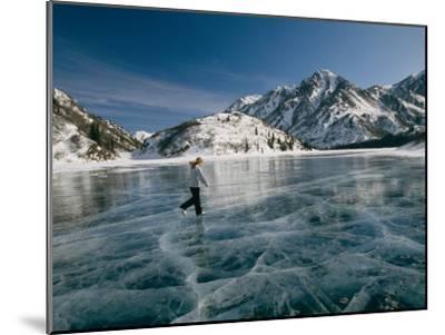 A Girl Ice Skates Across a Frozen Mountain Lake-Michael S^ Quinton-Mounted Photographic Print
