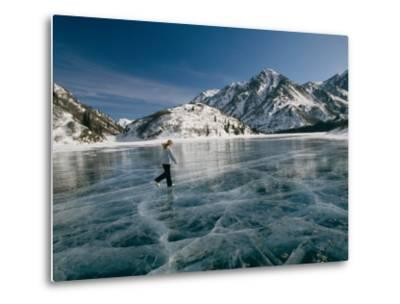 A Girl Ice Skates Across a Frozen Mountain Lake-Michael S^ Quinton-Metal Print