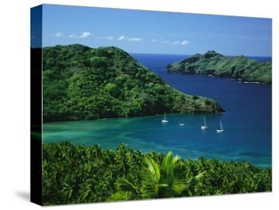 Sailboats Anchored in a Cove of Blue Water on an Asian Island-Tim Laman-Stretched Canvas Print