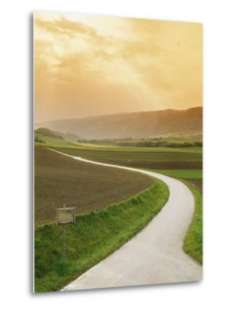 The Golden Sun Glows Through Cloud Cover to Illuminate a Country Road-Richard Nowitz-Metal Print
