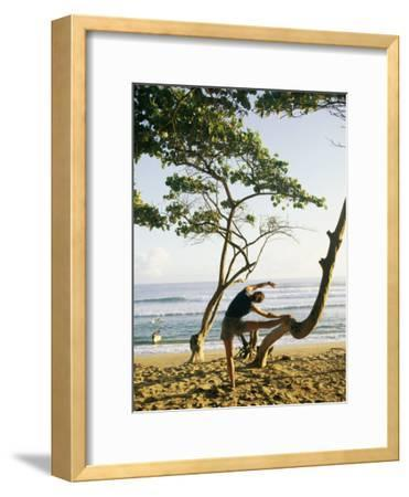 A Woman Stretches Her Body on a Small Tree at a Sandy Beach-Skip Brown-Framed Photographic Print