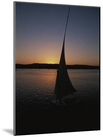 Sunset Outlines the Curve of a Felucca Sail on the Nile River-Stephen St^ John-Mounted Photographic Print