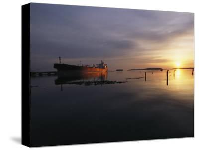 Twilight View of a Ship at Anchor in Still Water at Low Tide-Bill Curtsinger-Stretched Canvas Print