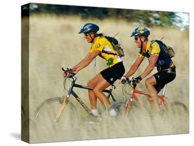 A Couple of Mountain Bikers Ride Along the Dirt Path-Barry Tessman-Stretched Canvas Print