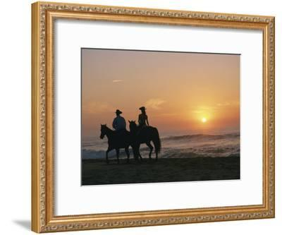 Two People on Horseback Ride Along an Ocean Shoreline at Sunset-Roy Toft-Framed Photographic Print