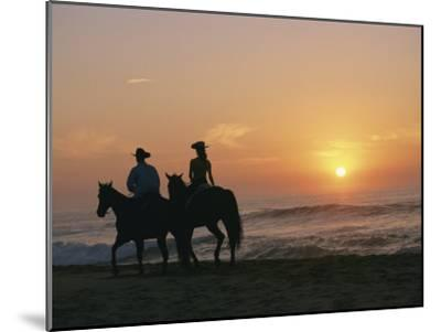 Two People on Horseback Ride Along an Ocean Shoreline at Sunset-Roy Toft-Mounted Photographic Print