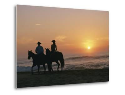 Two People on Horseback Ride Along an Ocean Shoreline at Sunset-Roy Toft-Metal Print