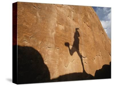 A Runners Shadow Falls on a Rock-Dugald Bremner-Stretched Canvas Print