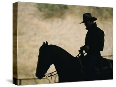 A Silhouette of a Rancher Riding a Horse-Dugald Bremner-Stretched Canvas Print