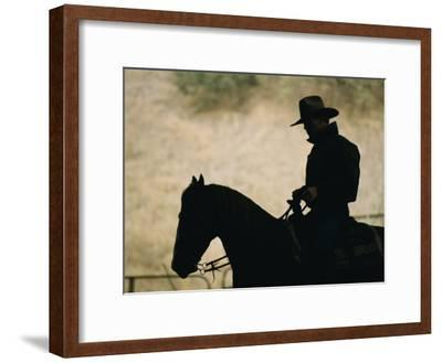 A Silhouette of a Rancher Riding a Horse-Dugald Bremner-Framed Photographic Print
