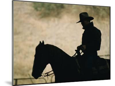 A Silhouette of a Rancher Riding a Horse-Dugald Bremner-Mounted Photographic Print