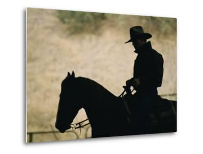 A Silhouette of a Rancher Riding a Horse-Dugald Bremner-Metal Print
