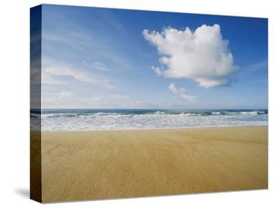 A Large Cloud Dominates the Sky as the Surf Rolls onto a Sandy Beach-Skip Brown-Stretched Canvas Print