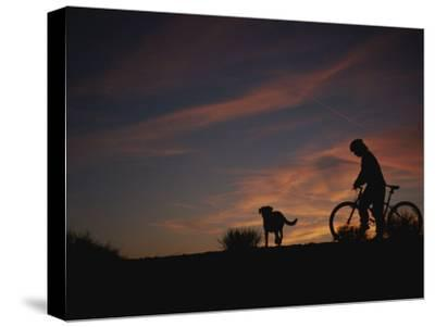 Bicyclist and Pet Silhouetted against a Sunset-Bobby Model-Stretched Canvas Print