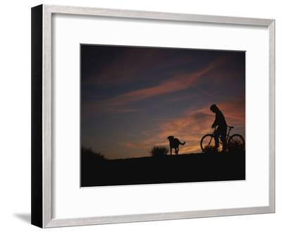 Bicyclist and Pet Silhouetted against a Sunset-Bobby Model-Framed Photographic Print
