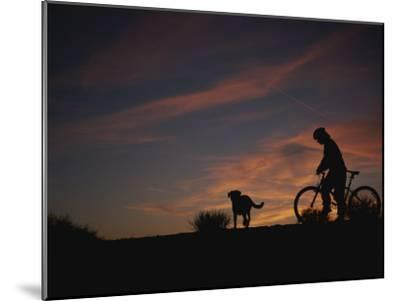 Bicyclist and Pet Silhouetted against a Sunset-Bobby Model-Mounted Photographic Print