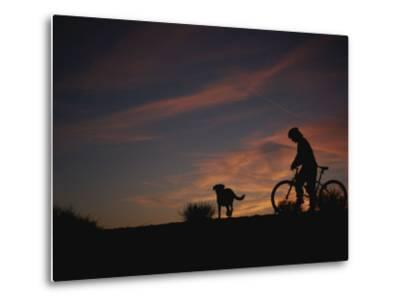 Bicyclist and Pet Silhouetted against a Sunset-Bobby Model-Metal Print