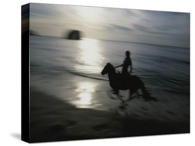 Horseback Rider Silhouetted on Beach, Costa Rica-Michael Melford-Stretched Canvas Print