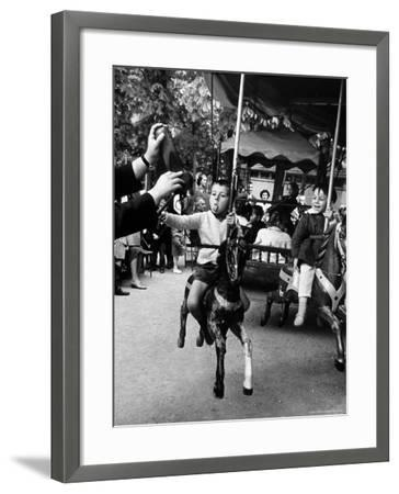 Little Boy on Merry Go Round at the Tuileries Gardens, Sticking Out His Tongue-Alfred Eisenstaedt-Framed Photographic Print