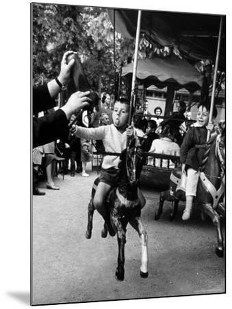 Little Boy on Merry Go Round at the Tuileries Gardens, Sticking Out His Tongue-Alfred Eisenstaedt-Mounted Photographic Print