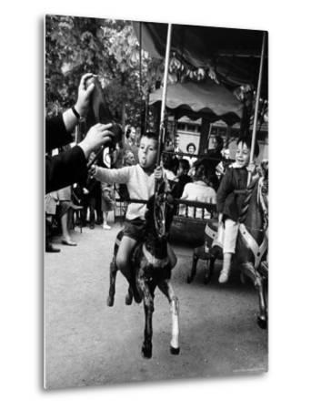 Little Boy on Merry Go Round at the Tuileries Gardens, Sticking Out His Tongue-Alfred Eisenstaedt-Metal Print