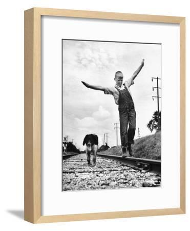 Larry Jim Holm with Dunk, His Spaniel Collie Mix, Walking Rail of Railroad Tracks in Rural Area-Myron Davis-Framed Photographic Print