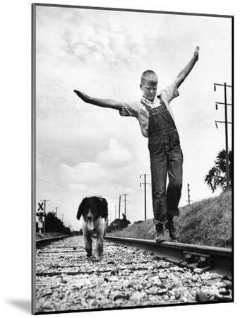 Larry Jim Holm with Dunk, His Spaniel Collie Mix, Walking Rail of Railroad Tracks in Rural Area-Myron Davis-Mounted Photographic Print