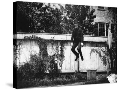 Man in a Suit and Bowler Hat Jumping in the Air in a Backyard in Brooklyn, Ny-Wallace G^ Levison-Stretched Canvas Print