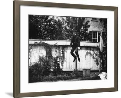 Man in a Suit and Bowler Hat Jumping in the Air in a Backyard in Brooklyn, Ny-Wallace G^ Levison-Framed Photographic Print