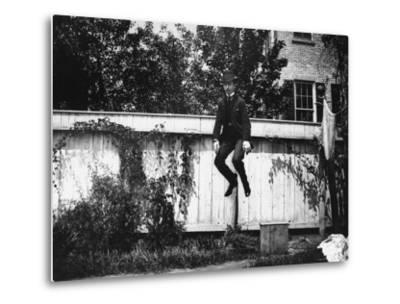 Man in a Suit and Bowler Hat Jumping in the Air in a Backyard in Brooklyn, Ny-Wallace G^ Levison-Metal Print