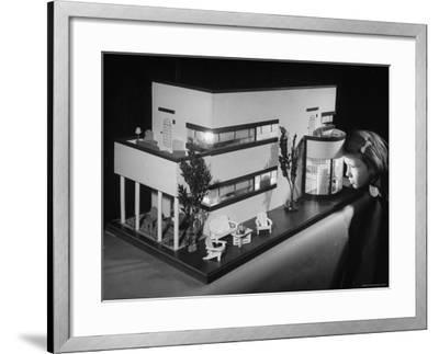 Little Girl Looking Into a Modern Doll House Being Sold at F.A.O. Schwarz-Herbert Gehr-Framed Photographic Print