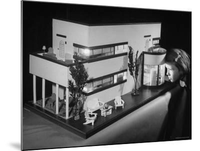 Little Girl Looking Into a Modern Doll House Being Sold at F.A.O. Schwarz-Herbert Gehr-Mounted Photographic Print