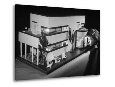 Little Girl Looking Into a Modern Doll House Being Sold at F.A.O. Schwarz-Herbert Gehr-Metal Print