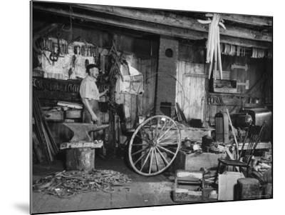 Blacksmith Working in His Shop-John Phillips-Mounted Photographic Print