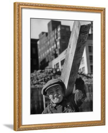 Construction Worker Carrying a Piece of Wood-Cornell Capa-Framed Photographic Print