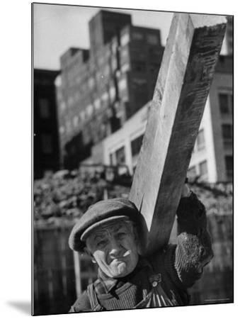 Construction Worker Carrying a Piece of Wood-Cornell Capa-Mounted Photographic Print