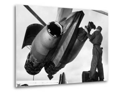 SAC's Maintenance Mechanic Sliding Into Barrel of Bomber's Jet Engine with the Help of His Partner-Margaret Bourke-White-Metal Print