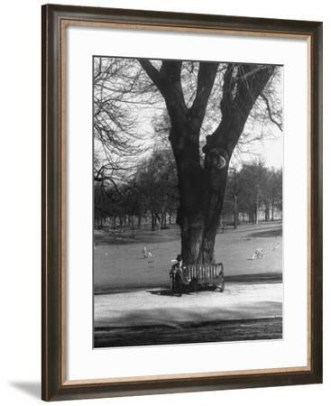 Man Sitting on a Bench and Reading a Newspaper in the Park-Cornell Capa-Framed Photographic Print
