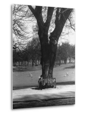 Man Sitting on a Bench and Reading a Newspaper in the Park-Cornell Capa-Metal Print