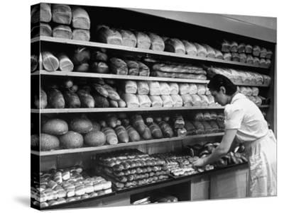 Good of Worker in Bakery Standing in Front of Shelves of Various Kinds of Breads and Rolls-Alfred Eisenstaedt-Stretched Canvas Print