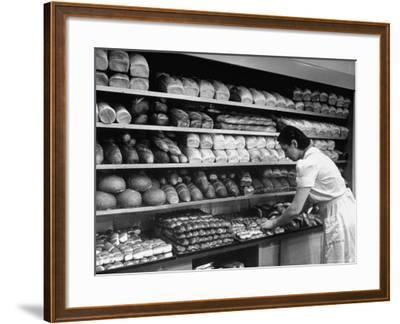 Good of Worker in Bakery Standing in Front of Shelves of Various Kinds of Breads and Rolls-Alfred Eisenstaedt-Framed Photographic Print