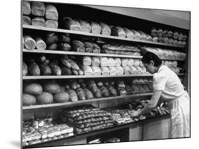Good of Worker in Bakery Standing in Front of Shelves of Various Kinds of Breads and Rolls-Alfred Eisenstaedt-Mounted Photographic Print