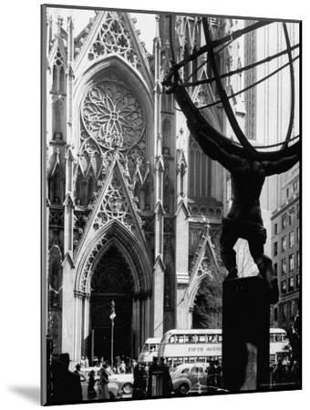 Entrance to St. Patrick's Visible Across Fifth Avenue, with Atlas Statue Silhouetted in Foreground-Andreas Feininger-Mounted Photographic Print
