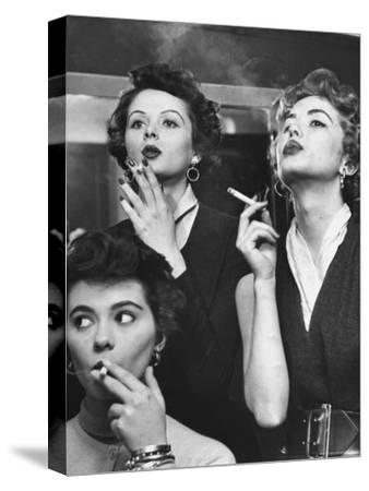 Models Exhaling Elegantly, Learning Proper Cigarette Smoking Technique in Practice For TV Ad-Peter Stackpole-Stretched Canvas Print