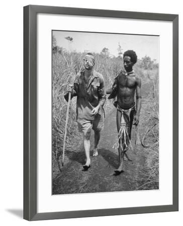 Papuan Native Helping a Wounded Australian Infantryman Along Road Away from the Buna Battlefront-George Silk-Framed Photographic Print