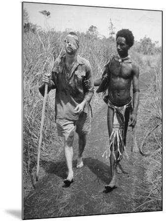 Papuan Native Helping a Wounded Australian Infantryman Along Road Away from the Buna Battlefront-George Silk-Mounted Photographic Print