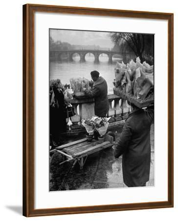 Parisian Flower Vendor at Work Stocking His Stall on the Seine with the Pont Neuf in the Background-Ed Clark-Framed Photographic Print