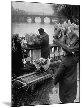 Parisian Flower Vendor at Work Stocking His Stall on the Seine with the Pont Neuf in the Background-Ed Clark-Mounted Photographic Print