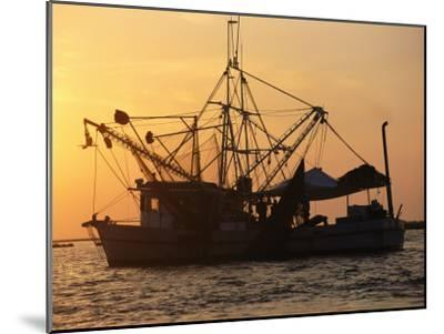 A Shrimp Boat Silhouetted against an Orange Sky--Mounted Photographic Print
